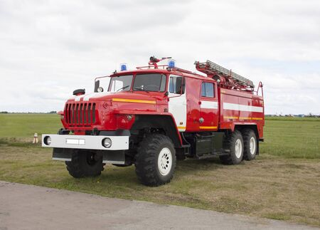 Russian fire truck of red color with retractable ladders stands on the airfield. Summer day, sky with clouds Banque d'images - 130501538