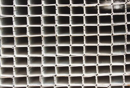 Industrial background. Pile of metal profile in a warehouse. Square metal pipe