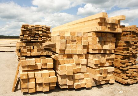 Lumber warehouse in the open air. Wooden beam, planks of wood, stacked in stacks. Sunny day, blue sky with clouds. Horizontal photo