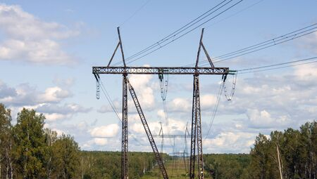 A high-voltage power line runs along a clearing among the trees. Sunny day, blue sky with clouds