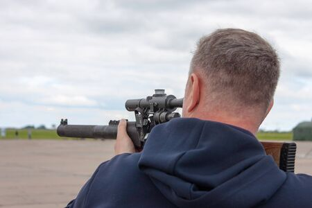 A short-haired man in a blue sweater with a hood is aiming from an army gun. Back view