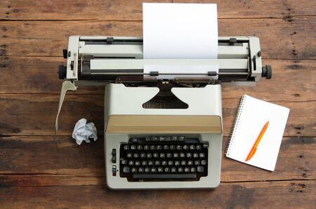 Vintage typewriter with the Cyrillic alphabet and a sheet of paper on an old table, a notebook on a spring and a pen