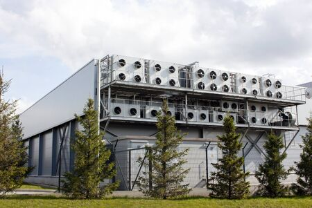 Factory building with lots of air conditioning. Green spruce and trimmed grass Imagens