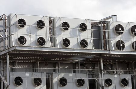 Several air conditioners on the gray wall of the factory. sunny day