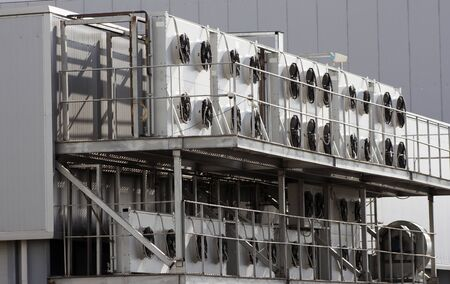Several large air conditioners on the gray wall of an industrial plant Imagens