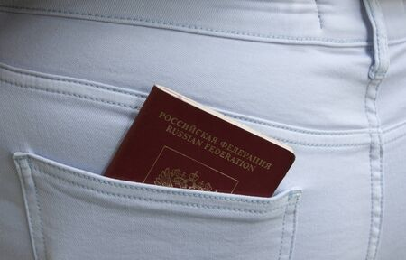 Foreign passport of the Russian Federation sticks out of the back pocket of blue jeans Foto de archivo