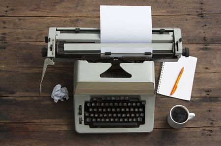 Antique typewriter with the Russian alphabet on an old table, a notebook on a spring and a pen, a cup of coffee