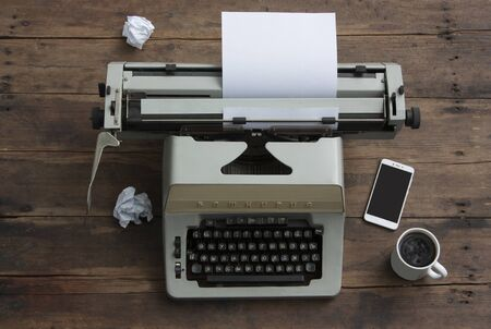 Antique typewriter with the Russian alphabet on an old table, mobile phone, cup of coffee 스톡 콘텐츠
