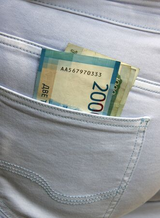 Banknotes of two thousand and one thousand Russian rubles stick out from the back pocket of blue jeans. The concept of poverty and wealth