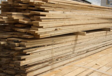 Lumber warehouse. Long wood planks stacked outdoors