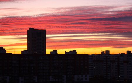 Beautiful dawn in a big city. High-rise, multi-storey buildings with many windows. The sky is pink and yellow