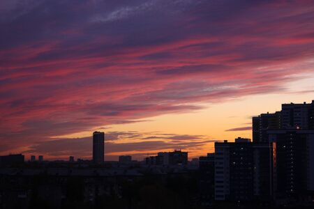 Beautiful sunrise in the city. Large, high-rise buildings with windows. The sky is pink and yellow