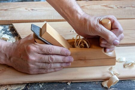 Mens hands hold a wooden jointer close-up. Light wood boards, shavings, sawdust Stock fotó