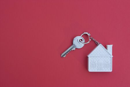 Key with a keychain in the form of a house on a red background. The concept of buying, selling, renting real estate, mortgages, your own home. Place for text Zdjęcie Seryjne