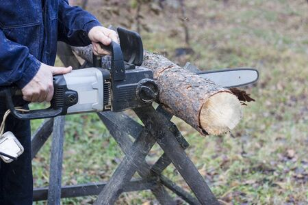 A man in blue uniform cuts pine wood with an electric saw. Horizontal photo