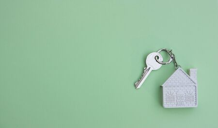White key with a keychain in the form of a house on a light green background. The concept of buying, selling, renting real estate, mortgages, your own home. Place for text Stockfoto