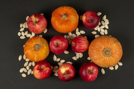 Orange pumpkins, red apples and pumpkin seeds on a black background. Natural nutrition. Vegan food Stock fotó