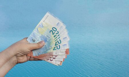 Hand with euro bills of 10 and 20 on a background of azure sea water. The concept of wealth and relaxation on the beach Reklamní fotografie - 135502651