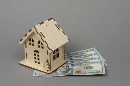 A small wooden house and bills for 100 dollars. The concept of buying, selling, renting housing and real estate, a mortgage, your own home. Place for text
