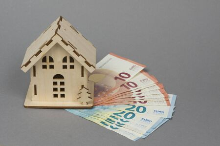 A small wooden house and notes for 20 and 10 euros. The concept of buying, selling, renting housing and real estate, a mortgage, your own home. Place for text