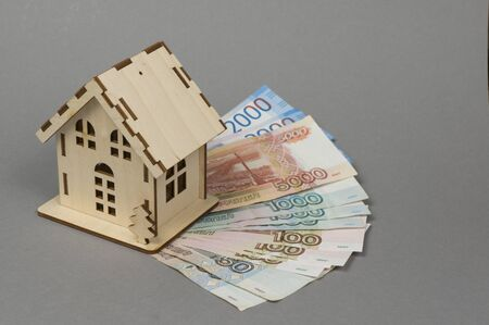 A small wooden house and banknotes Russian rubles. The concept of buying, selling, renting housing and real estate, a mortgage, your own home. Place for text