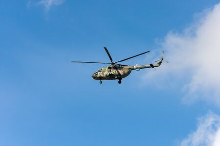 The military helicopter against the blue sky. 免版税图像