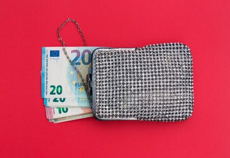 Banknotes of 20 and 10 euros in a shiny vintage handbag with rhinestones on a red background. The concept of wealth or poverty of an elderly woman