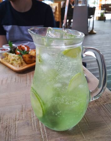 Lemonade in a large decanter with ice, slices of lemon and a plastic straw on a table in a cafe