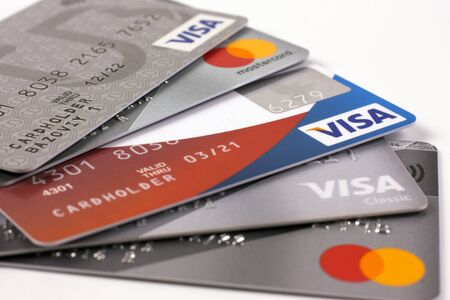 February 11, 2020. Novosibirsk, Russia. Several bank credit cards with Visa and Mastercard logos on a white background