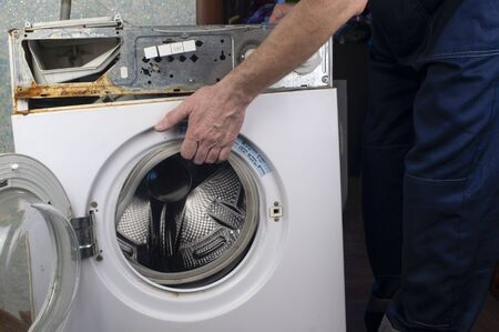 Repair of washing machines, repair of large household appliances. Repairman disassembles a washing machine for parts