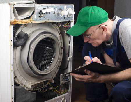 Repair of washing machines, repair of large household appliances. The master examines the disassembled washing machine and records faults