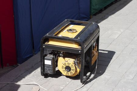 A powerful portable gas or diesel generator to provide electricity to tents with goods. Standing on the sidewalk