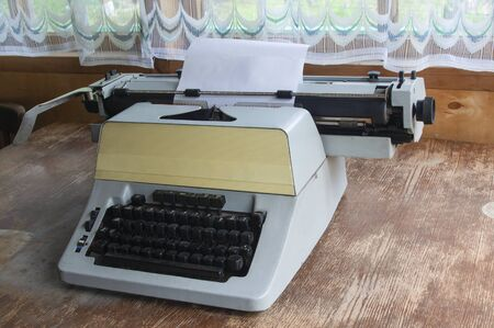 In a country house with wooden walls and transparent curtains, a typewriter stands on an old wooden table