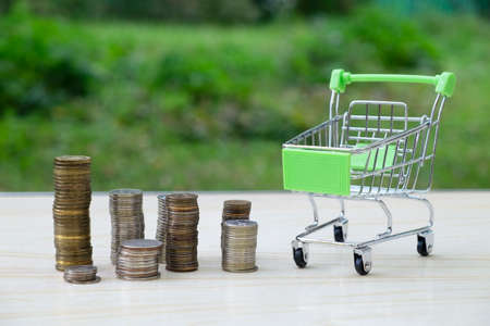 Trolley for groceries and goods from the supermarket and a lot of coins. Business concept, trade, poverty, wealth Stock fotó - 154789326