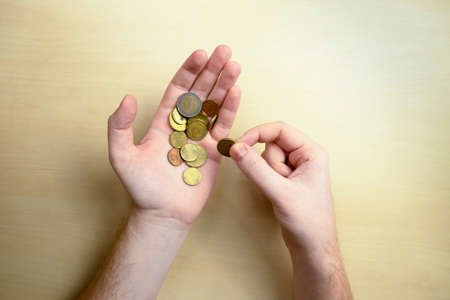 Euro cents in the hands on the left palm. Financial crisis concept, poverty