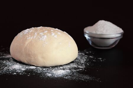 Yeast dough and bowl with flour on a dark background