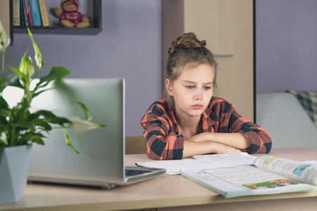 A girl sits at the table at home, does homework with a laptop and cries Stock Photo