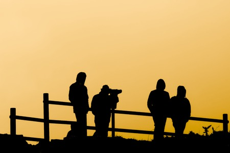 four friends looking through a telescope in a lookout point at sunset