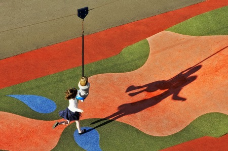 two children playing in the park with ziplines producing long shadows photo