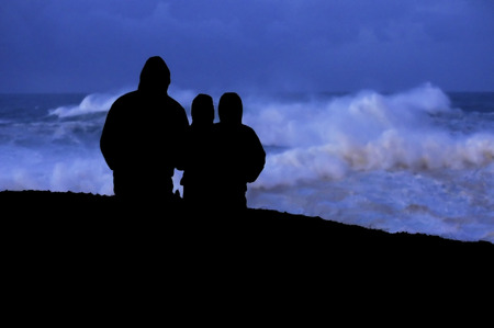 power giant: people look at dusk giant waves in sea storm in Corunna  Spain Stock Photo