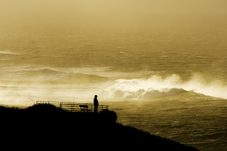 wavely: men look at sunset giant waves in sea storm in Corunna  Spain