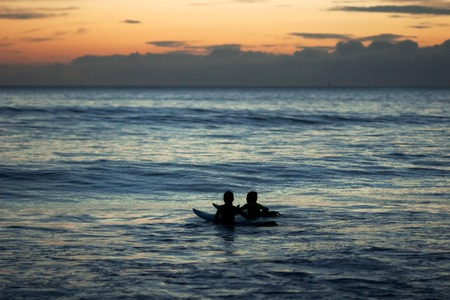 two surfers children talking at sea at dusk in Doninhos Galicia Beach