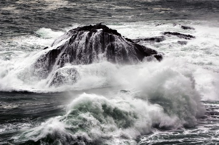 wavely: rocky islet with giant waves in sea storm at dusk in sea storm in Corunna  Spain Stock Photo