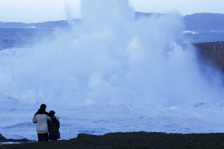 couple look at dusk giant waves in sea storm in Corunna  Spain