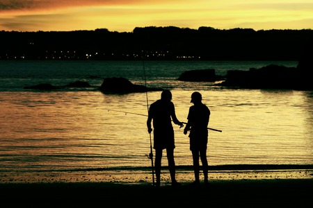 father and son fishing on the beach at dusk photo