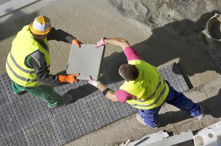 street worker repairing sidewalks and pipelines in the city photo