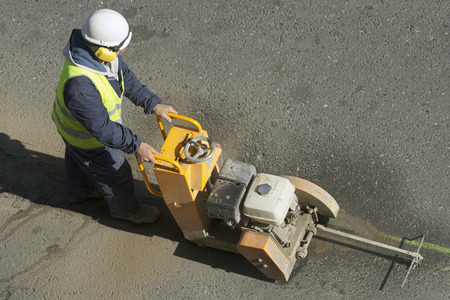 city road: worker using cutting  pavement machine in the city road