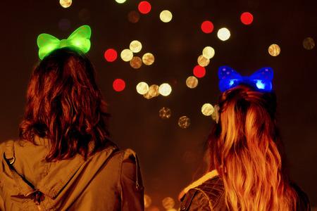 fiestas: two girls watching fireworks on the night of Saint  John  Hogueras de San Juan  in Coruna  Spain