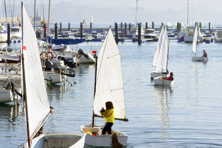 and an optimist: children learn to sail on optimist sailboat in Galicia Spain Stock Photo