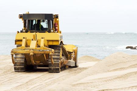 heavy equipment operator: yellows excavators on the city  beach working sand moving in Corunna Spain Stock Photo